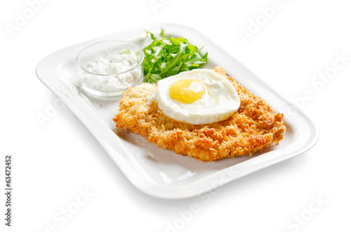 pork chop breaded and fried eggs on a white background