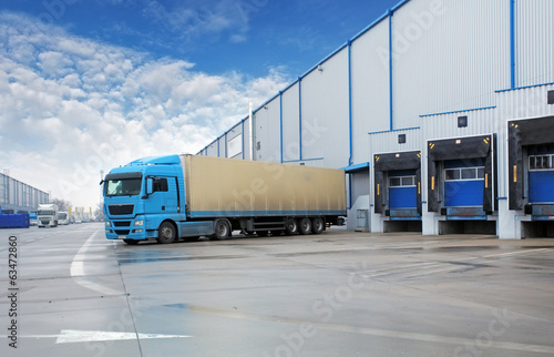 canvas print picture Unloading cargo truck at warehouse building