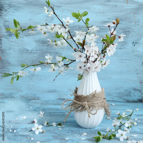 blossom apple tree in vase on blue background