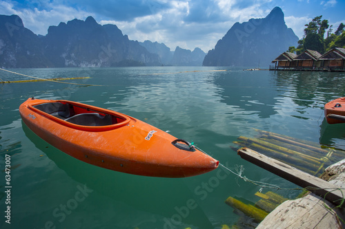 Orange kayak floating on green water, khaosok, thailand