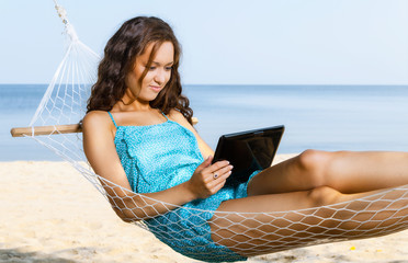 Woman relaxing on hammock and using digital tablet