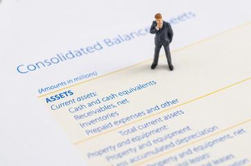 miniature businessman stand on the balance sheet