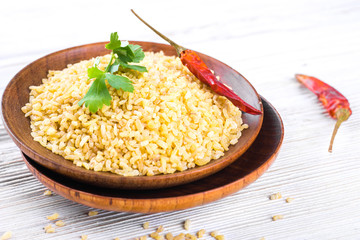 Bulgur in a wooden plate with red pepper