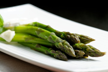 Close up of fresh green asparagus with  a fresh cheese