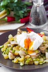 Hot salad with potatoes, ham, peas, mushrooms, poached egg