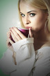 Beautiful blond woman drinking a Tea. Vapor Cup of Coffee. Hot