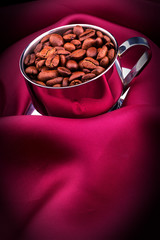 cup of Coffee with beans on red silk