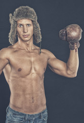 Shirtless man raised his hands in boxing gloves