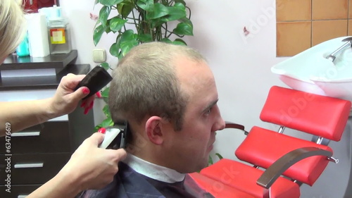 Barber hand cutting customer man head hair with clipper in salon
