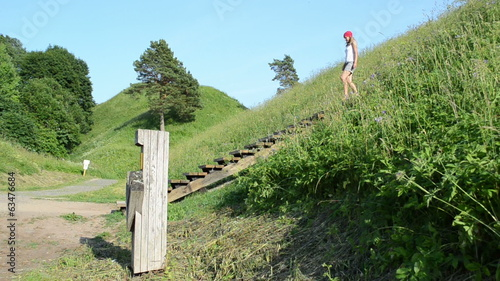 tourist woman girl descend wooden stairs from mound hill