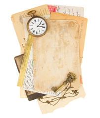 pile of old photos and papers with antique clock