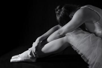 Female dancer sit on floor looking sad in pink tutu low key
