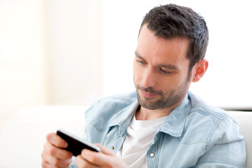 Young relaxed man sending text in a sofa