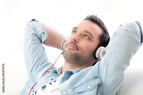 Young relaxed man listening music in a sofa