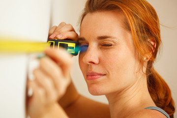 Portrait of young woman with measuring tape.