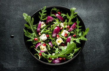Fresh spring salad with rucola, feta cheese and red onion