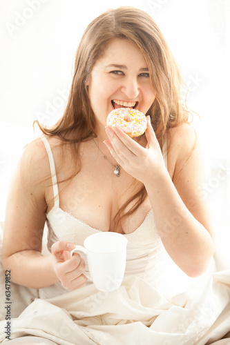 woman eating donut and drinking coffee in bed