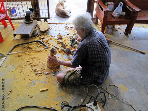 Carver old man carving wood figure buddha at Thailand