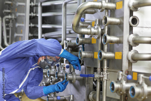 Technician in overalls maintaining technological system in plant