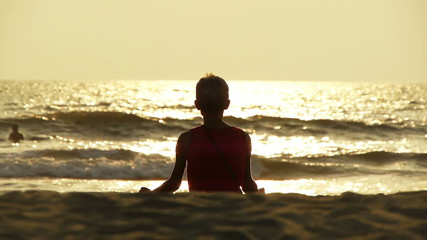 Practicing yoga on Goa beach at sunset