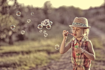 carefree girl lets soap bubbles on a warm day
