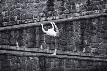 back view of topless man stretching at stony wall