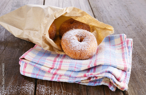 Sugar powdered cinnamon doughnuts in paper bag