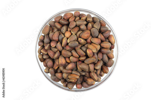 small pine nuts in a glass bowl on a white background