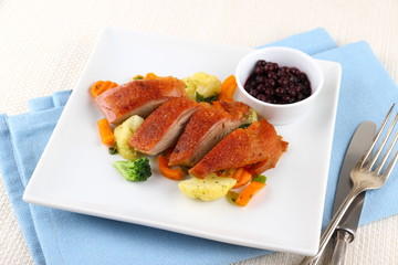 Roasted duck breast with vegetables and cutlery