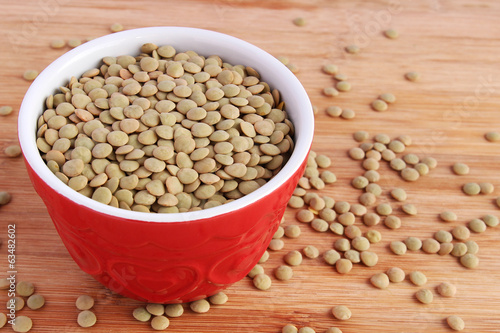 Dry green lentils in red bowl on wooden board
