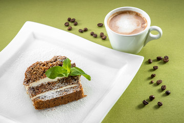 A slice of carrot cake on green background with coffee