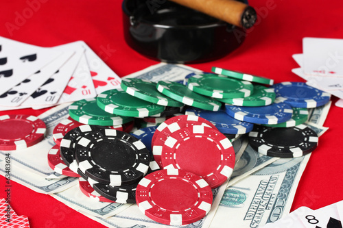 The red poker table with playing cards, poker chips and dollars