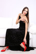 Beautiful young woman in black dress on sofa on white