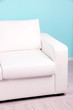 White sofa close-up in room on blue background