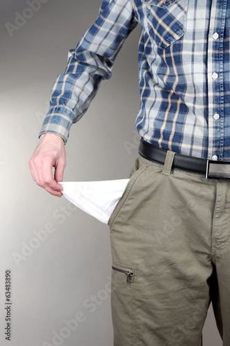 Man showing his empty pocket on grey background