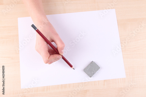 Hand holding pencil and erase with paper on wooden background