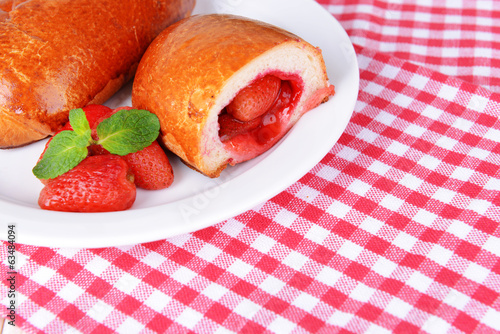 Fresh baked pasties with strawberries on plate on table