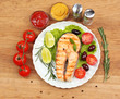 Tasty grilled salmon with vegetables, on wooden table