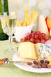 Assorted cheese plate , grape and wine glass