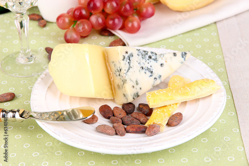 Assorted cheese plate, cocoa beans and grape on pink close-up