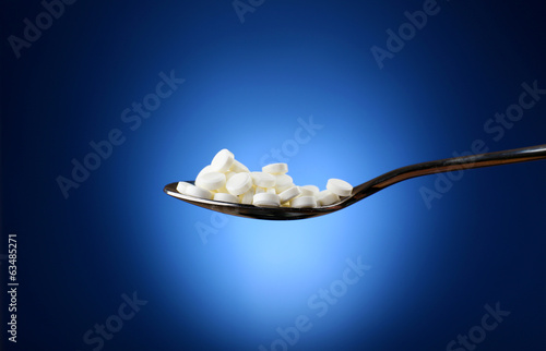 Medical pills on spoon on blue background