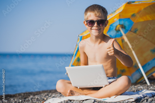 happy smiling boy is sunbathing on a beach