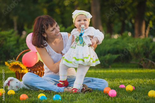 baby and mom are playing in the green park