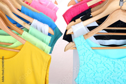Different clothes on hangers on light background