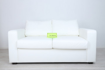 New white sofa with price on light background