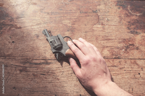 Hand with gun at table