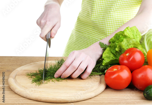 Female hands chopping dill