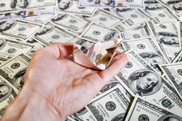 The hand with the ship of rubles over  dollar bills