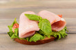 Delicious sandwich with lettuce and ham on table close-up