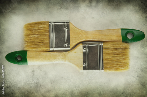 Two paint brushes on grunge background